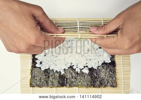 closeup of a young man preparing makizushi, rolling a bamboo mat with the nori, the rice and the stuffing inside it