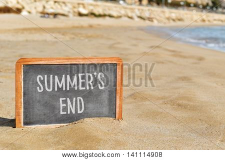 closeup of a chalkboard with the text summers end written in it, on the sand of a beach