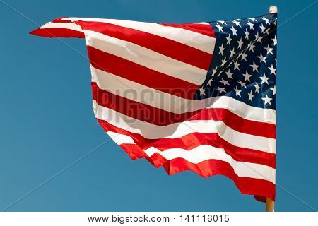 United States flag blows in the wind against a dark blue sky attached to the wall from the side.
