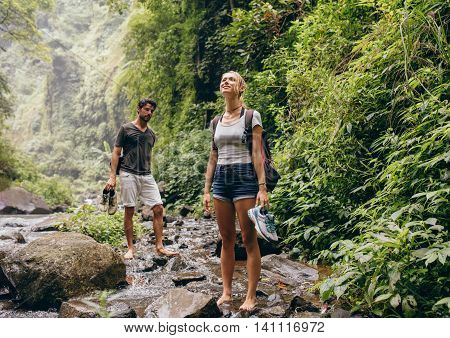 Couple On Forest Hike Walking By A Creek