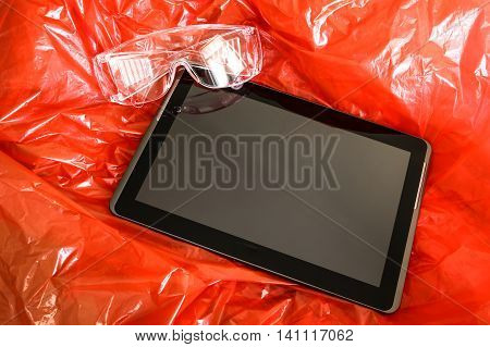 A Tablet Pc on red synthetic protective material with security glasses for safety.