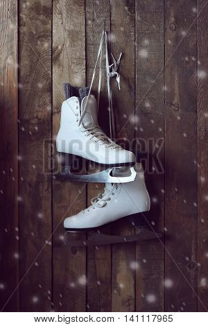 The white female skates for figure skating hang on laces on a wall from boards.