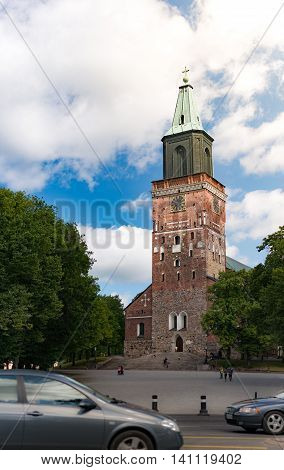Turku Cathedral on sunny day with blue cloudy sky in background and city street with cars in foreground