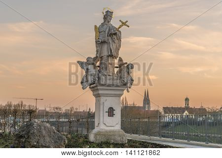 Holy statue in Regensburg with dome St. Peter in the background during sunset