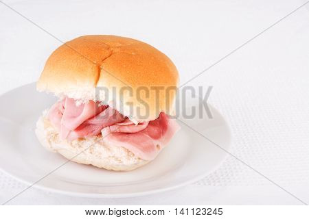 Ham bread roll or bap on a white plate