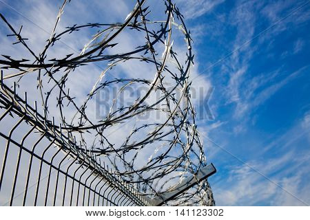 Barbed wire fence with blue skies and clouds in the background