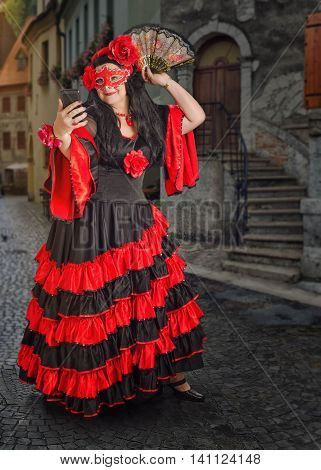 Masked flamenco dancer takes photo with mobile phone posing with fan.  The mature woman wears red and black flamenco floor-length gown with frills