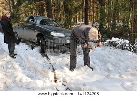 Saint-Petersburg, Russia - April 10, 2010: Russian-made Lada car was stuck in a forest snow-covered road. The driver tries to pull the car