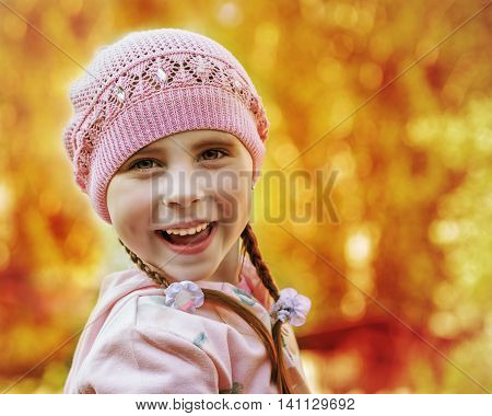Happy child smiling on a background of autumn foliage of trees.