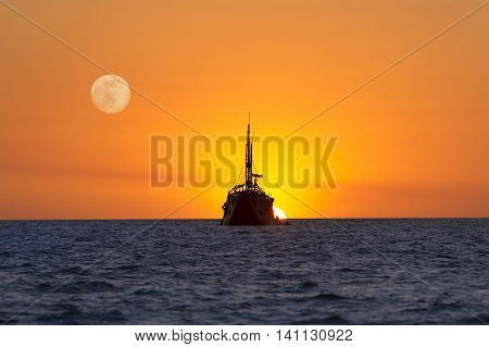 Ship Sunset is a detailed silhouette of a large old wooden ship as it sits at sea and watches the sun set on the ocean horizon as the moon rises in the sky.