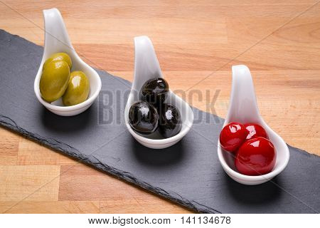 Delicious olives in spoons on a slate serving tray