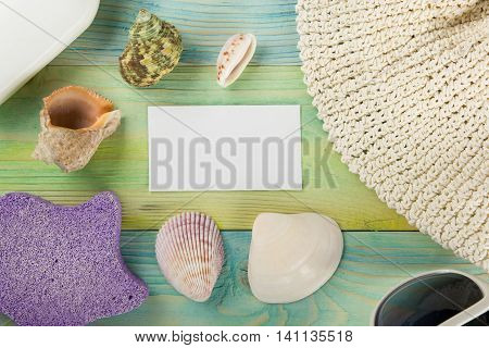 Summer sea vacation background with white blank business card Notebook blank page with Travel items on blue green wooden table. Sea shells, pebbles, top view mockup