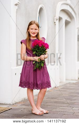 Portrait of adorable little girl of 8-9 years old, holding beautiful bouquet of bright pink roses
