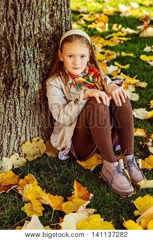 Autumn portrait of adorable little blond girl of 8 years old, wearing beige trench coat, brown tights and shoes, sitting on a grass under the tree
