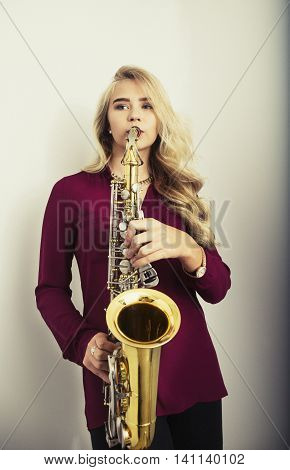 Beautiful young woman with long blond hair playing saxophone
