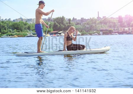 Young Couple Smiling Paddling On Sup Board02