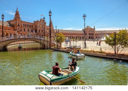 Seville, Andalusia, Spain - April 18, 2016: boats with tourists on the canal surrounding the Plaza de Espana on a sunny day.