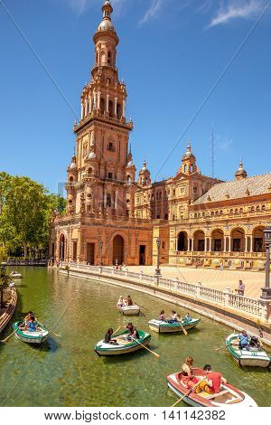 Seville, Andalusia, Spain - April 18, 2016: aerial view of tower in Spain Square, Plaza de Espana, and several boats in the canal surrounding the popular square.