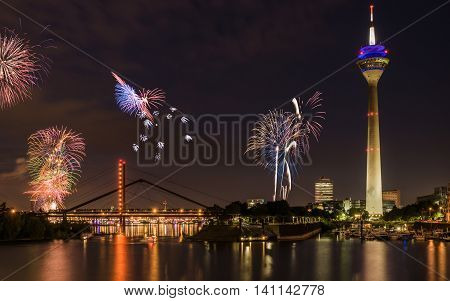Dusseldorf harbor basin during night. Fireworks in the old town