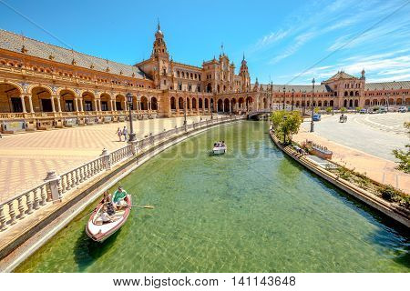 Seville, Andalusia, Spain - April 18, 2016: panoramic view of boats with tourists on canal surrounding the Plaza de Espana or Spain Square in a sunny day.