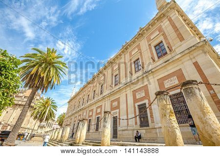 Seville, Andalusia, Spain - April 18, 2016: the facade of the Casa Lonja with the Archive of the Indies, Plaza del Triunfo in Seville's old town.