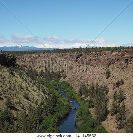 r he Deschutes River winds through G deep canyon with the Cascade Mountains in the background.