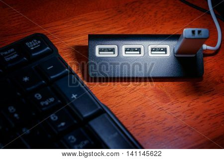 Black USB hub with memory card on the table near black keyboard under USB lamp