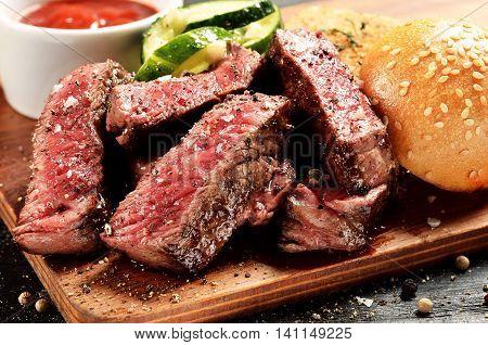 Prime Black Angus Steak burger. Medium Rare degree of steak doneness.