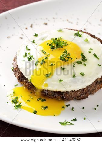 Beef Steak with fried egg on white plate. Flowing yolk.