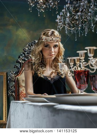 young blond woman wearing crown in fairy luxury interior with empty antique frames total wealth concept