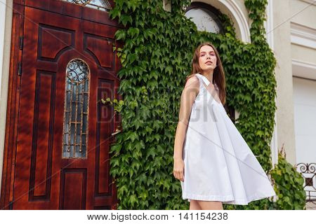 Beautiful young brunette girl in white dress goes down the stairs against of an old house architecture