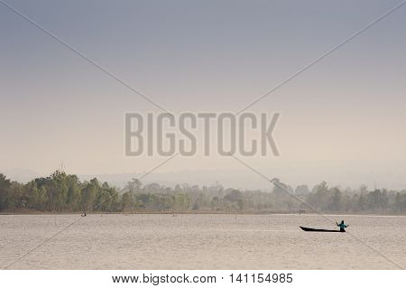 Silhouetted Traditional Wooden Canoes Fishing In Asia