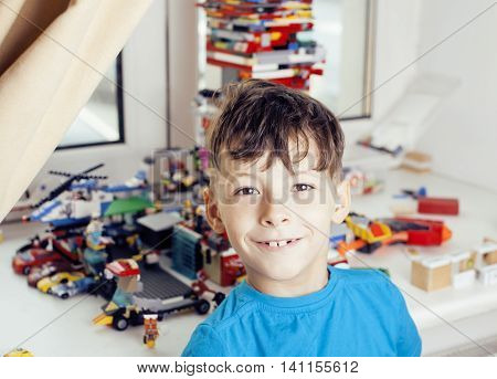 little cute preschooler boy playing lego toys at home happy smiling, lifestyle real children concept