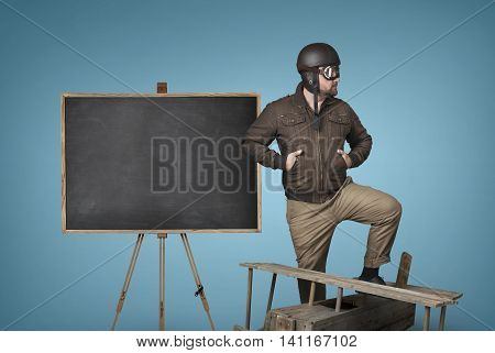 Empty blackboard with businessman on pilot outfit and wooden plane