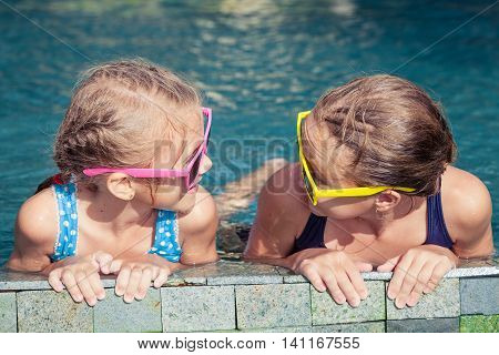 Two happy children playing on the swimming pool in aqua park at the day time. Concept of friendly family.