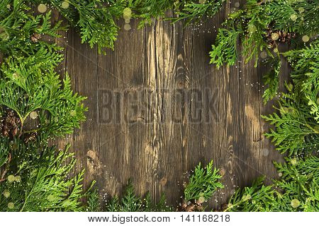 Cedar branches over wooden background. Greeting card. Top view. Space for text