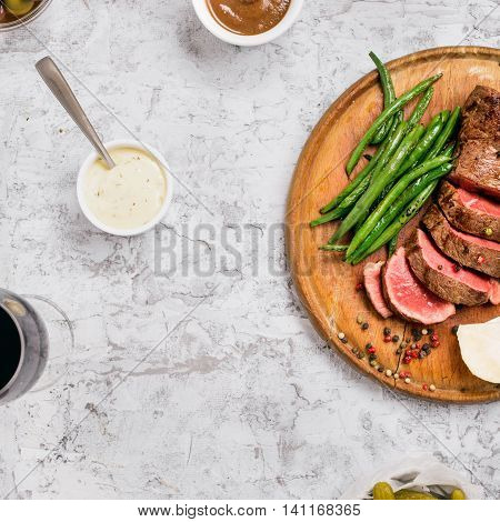 Sliced medium rare grilled steak with French bean on a wooden board on a white surface with sauces and red wine top view space for text
