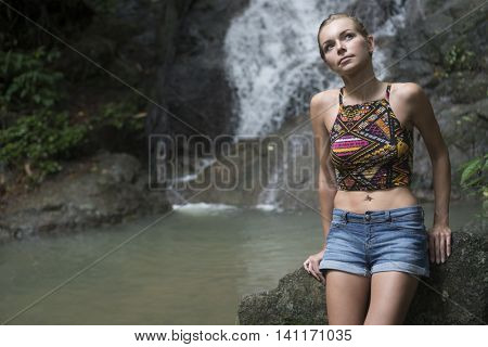 Pretty blonde woman sittting on a rock and looking up near waterfall. Female tourist enjoying by a water fall in forest