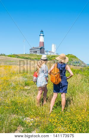 Two girls looking at Montauk Point Lighthouse - Long Island, US
