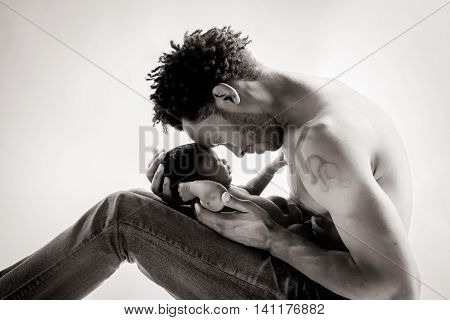 A loving African American father holds his newborn daughter gently and closely. He is shirtless and she reaches up with one hand to touch his chest. There foreheads are touching. Black and White