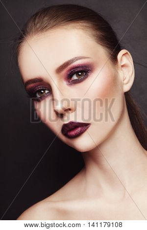Portrait of young beautiful woman with stylish dark eyeshadow and lipstick