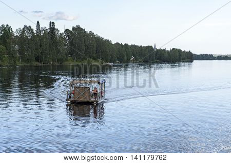 GRANO, SWEDEN ON JUNE 25. View of a wooden raft on the calm river on June 25, 2016 in Grano, Sweden. Unidentified people on board. Village in the background. Editorial use.