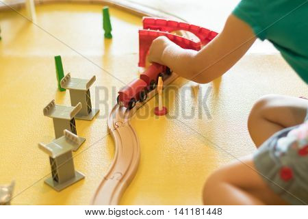 young girl playing with wooden train set on a yellow playroom floor