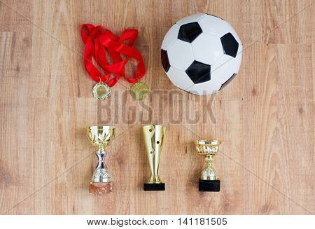 sport, achievement, championship, competition and success concept - football or soccer ball with golden medals and cups over wooden background
