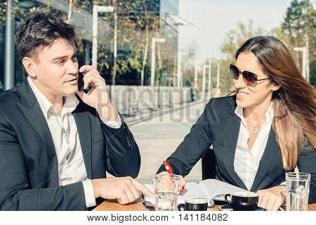 Business manager with his assistant outdoors in caffee