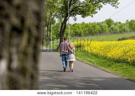 Couple in love - walking. In background rape field.