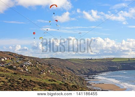 Paragliders flying above Freathy in Cornwall, England