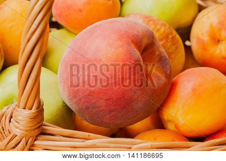 Bright peach close-up lying in wicker basket with other summer fruit. Low Calorie, for digestive tract, healthy heart , from wrinkles, excess salt from body, restore hormonal balance, male strength