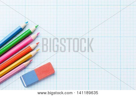 Colorful pencils over millimeter lined paper. Top view with copy space