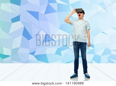 3d technology, virtual reality, entertainment, cyberspace and people concept - amazed young man with virtual reality headset or 3d glasses over low poly background